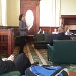 A group sits listening to a speaker at the Massachusetts State House.