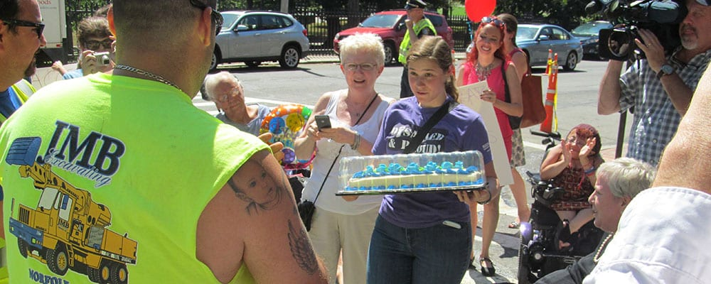 A person holds a cake as they speak to a person wearing a sleeveless t-shirt.