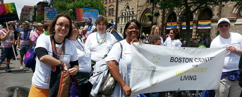 People in white t-shirts hold Boston Center for Independent Living banner at pride march.