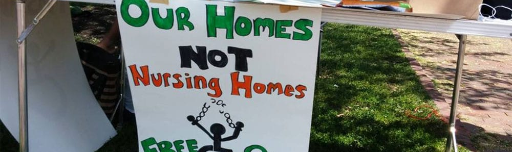 "Signs reads ""Our Homes Not Nursing Homes"""