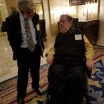 A guest in a black suit speaks with a guest in a wheelchair wearing a black vest.