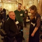 Two people and a person in a wheelchair talk to each other in the ballroom.