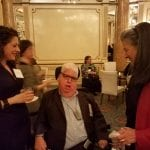 Two people and a person in a wheelchair talk to each other in the ballroom over drinks.