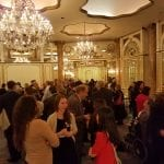 Wide view of the guests having drinks in the ballroom.