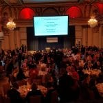 Wide view of the ballroom as guests have dinner.