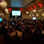 Wide view of the ballroom as speaker addresses audience.