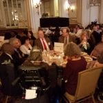 A table of guests have dinner and make conversation.