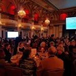 Wide view of the guests having dinner in the ballroom.