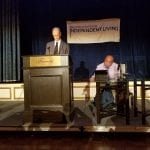 A speaker wearing a dark gray suit stands at the podium and reads from a prompt while a speaker in a lavender dress shirt sits in a wheelchair to the right of the podium reading from a tablet.