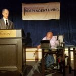 A speaker wearing a dark gray suit stands at the podium while a speaker in a lavender dress shirt sits in a wheelchair to the right of the podium reading from a tablet.