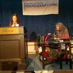 A person stands at the podium speaking to the audience while a person in a power wheelchair watches nearby.