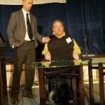 Person in wheelchair is talking while person in dark gray suit holds the mic.