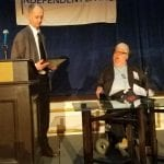 Person in wheelchair is given an award by person at podium.