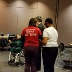 A person wearing a red t-shirt that reads Advocacy, Service, Action! helps a person wearing a white t-shirt.