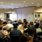 Wide view of the meeting hall as attendees have dinner.