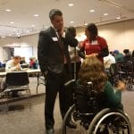 A person in a black suit speaks to a person in a wheelchair.