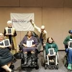 Four honorees in wheelchairs smile for photo while honoree with white cane and person in yellow shirt holds fist in air.
