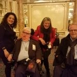 Two guests stand with two other guests seated in wheelchairs for a group photo.
