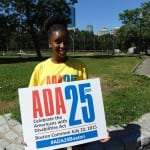 Person holds ADA 25 sign wearing yellow ADA 25 t-shirt.