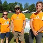 Three people wear orange t-shirts from All Out Adventures.