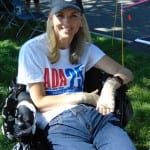 A person wearing an ADA t-shirt sits in a wheelchair and smiles for a picture.