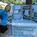 A person in a blue NILC t-shirt stands next to an information table from the Northeast Independent Living Program.
