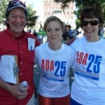 Two people wearing white ADA 25 t-shirts smile for a photo with a person in a red shirt.
