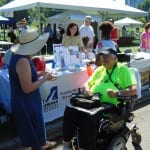 A person in a wheelchair and neon t-shirt converses with a person in a blue dress.