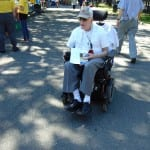 A person in a wheelchair holds pamphlets.