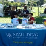 Three people work at the Spaulding Rehabilitation Network information table.