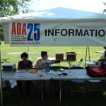 Two people are seated at an information tent.