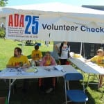 Five people at the volunteer check-in tent.