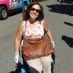 A person in a colorful shirt holding a borwn leather bag smiles for a photo from her wheelchair.