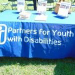 "Tablecloth reads ""Partners for Youth with Disabilities."""