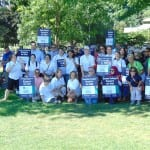 A large crowd of people pose for a group photo holding signs. Sign reads Supports the ADA along with various organization names.