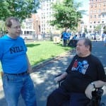 A person in a black ADA 25 t-shirt speaks with a person in a blue NILP t-shirt.