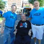 A person in a black ADA 25 t-shirt takes a photo with two people in blue NILP t-shirts.