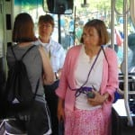 Person speaks to a bus driver while person wearing pink clothing walks by.