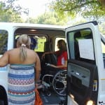 A group of people help a person in a wheelchair out of a handicapped van.