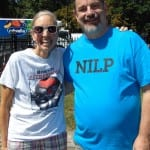 A person wearing a blue NILP shirt and a person wearing a white t-shirt take a picture together.