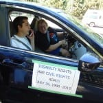 "Two people smile from car interior. Sign reads ""Disability Right are Civil Rights""."