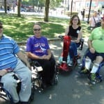 Four people in wheelchairs smile for a group photo.