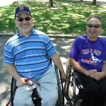 Two people in wheelchairs smile for a group photo.