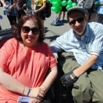 Two people in wheelchairs smile for a photo.