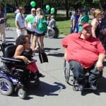 A person in an electric wheelchair and a person in manual wheelchair with a red hat and polo speak to someone out of frame.