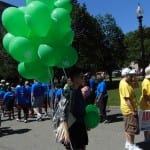 A person walks among the attendees carrying green balloons.