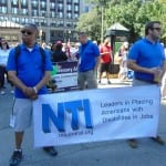 Two people hold a banner for NTI Central at the ADA 25 Celebration