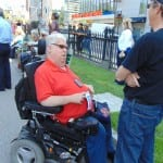 A person wearing a black t-shirt speaks to a person in a red polo seated in a wheelchair.