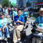 Three people in blue shirts sit in wheelchairs amidst a group of protesters at Boston Common.