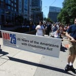 Two people carry the ADA 25 banner.